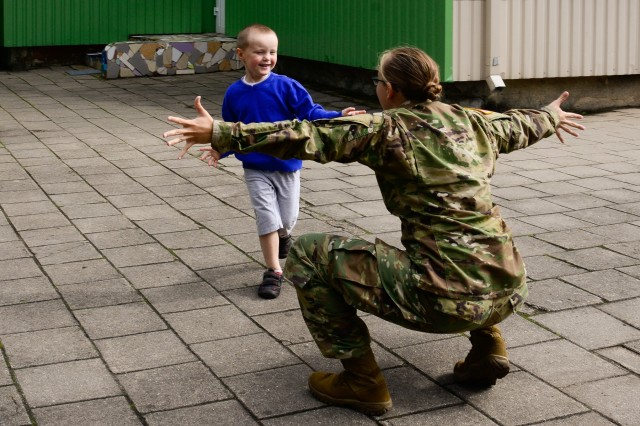 U.S. Army Spc. Stephanie Lish, assigned to Alpha Company, 457th Civil Affairs Battalion, 361st Civil Affairs Brigade, 7th Mission Support Command, prepares to hug a child from Kudikiu Namai during a Humanitarian Civil Assistance (HCA) project, in Sauliai, Lithuania, August 23, 2016. As part of the European Command's (EUCOM) Humanitarian and Civic Assistance Program, the 375th Engineer Company, 457th Civil Affairs Battalion and the Lithuanian military collaborate to renovate the fence at Kudikiu Namai, an orphanage for Lithuanian children up to the age of 6, in Sauliai, Lithuania, August 8-26, 2016. (U.S. Army Photo by Pfc. Emily Houdershieldt)