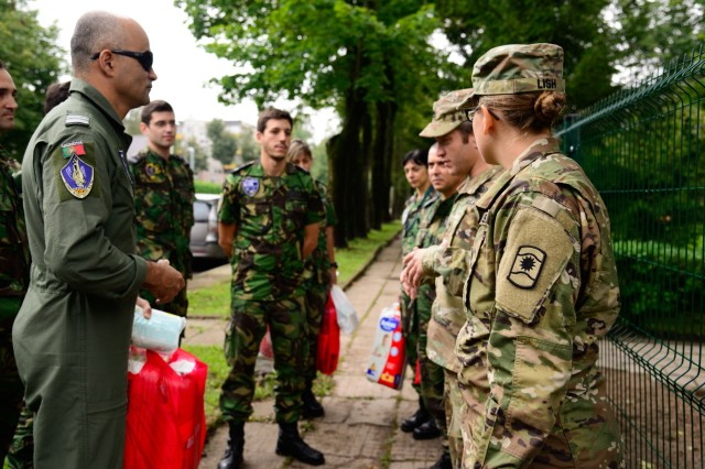 U.S. Soldiers, assigned to Alpha Company, 457th Civil Affairs Battalion, 361st Civil Affairs Brigade, 7th Mission Support Command, greet Portuguese airmen before they enter Kudikiu Namai during a Humanitarian Civil Assistance (HCA) project, in Sauliai, Lithuania, August 18, 2016. As part of the European Command's (EUCOM) Humanitarian and Civic Assistance Program, the 375th Engineer Company, 457th Civil Affairs Battalion and the Lithuanian military collaborate to renovate the fence at Kudikiu Namai, an orphanage for Lithuanian children up to the age of 6, in Sauliai, Lithuania, August 8-26, 2016. (U.S. Army Photo by Pfc. Emily Houdershieldt)