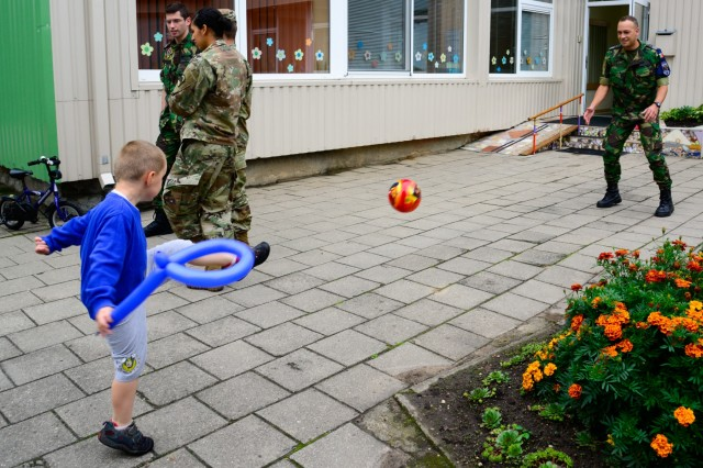 A Portuguese airman plays with a child from Kudikiu Namai during a Humanitarian Civil Assistance (HCA) project, in Sauliai, Lithuania, August 23, 2016. As part of the European Command's (EUCOM) Humanitarian and Civic Assistance Program, the 375th Engineer Company, 457th Civil Affairs Battalion and the Lithuanian military collaborate to renovate the fence at Kudikiu Namai, an orphanage for Lithuanian children up to the age of 6, in Sauliai, Lithuania, August 8-26, 2016. (U.S. Army Photo by Pfc. Emily Houdershieldt)