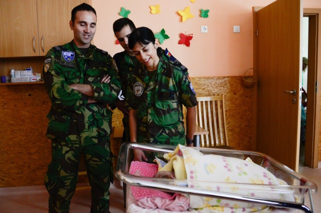 Portuguese airmen greet a baby from Kudikiu Namai during a Humanitarian Civil Assistance (HCA) project, in Sauliai, Lithuania, August 23, 2016. As part of the European Command's (EUCOM) Humanitarian and Civic Assistance Program, the 375th Engineer Company, 457th Civil Affairs Battalion and the Lithuanian military collaborate to renovate the fence at Kudikiu Namai, an orphanage for Lithuanian children up to the age of 6, in Sauliai, Lithuania, August 8-26, 2016. (U.S. Army Photo by Pfc. Emily Houdershieldt)