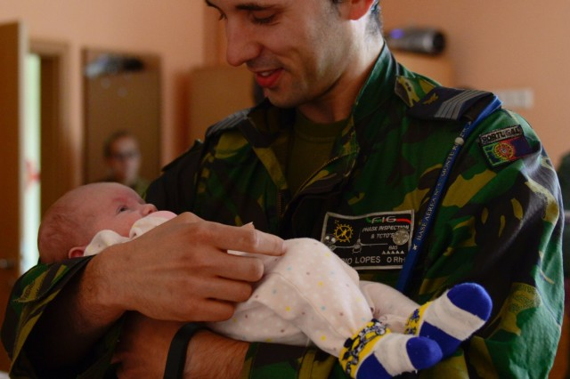 A Portuguese airman holds a baby from Kudikiu Namai during a Humanitarian Civil Assistance (HCA) project, in Sauliai, Lithuania, August 23, 2016. As part of the European Command's (EUCOM) Humanitarian and Civic Assistance Program, the 375th Engineer Company, 457th Civil Affairs Battalion and the Lithuanian military collaborate to renovate the fence at Kudikiu Namai, an orphanage for Lithuanian children up to the age of 6, in Sauliai, Lithuania, August 8-26, 2016. (U.S. Army Photo by Pfc. Emily Houdershieldt)