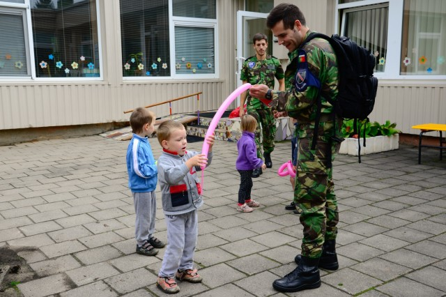 A Portuguese airman creates balloon sculptures for children from Kudikiu Namai during a Humanitarian Civil Assistance (HCA) project, in Sauliai, Lithuania, August 23, 2016. As part of the European Command's (EUCOM) Humanitarian and Civic Assistance Program, the 375th Engineer Company, 457th Civil Affairs Battalion and the Lithuanian military collaborate to renovate the fence at Kudikiu Namai, an orphanage for Lithuanian children up to the age of 6, in Sauliai, Lithuania, August 8-26, 2016. (U.S. Army Photo by Pfc. Emily Houdershieldt)