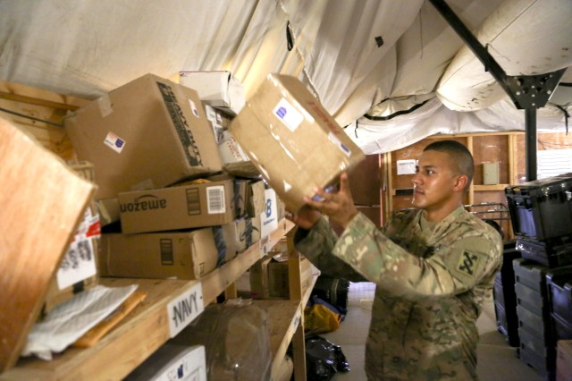 Cpl. Luis Delgado, the remote site's noncommissioned officer in charge with Alpha Detachment of 4th Platoon, 912th Human Resource Company, 90th Human Resource Company, 17th Special Troops Battalion, 17th Sustainment Brigade, 1st Sustainment Command (Theater), sorts mail in the back of the mail tent at a base in Southwest Asia, August 15, 2016. As a junior NCO, Delgado has a rare opportunity to lead a location and has even briefed base leaders on how the mail process works.