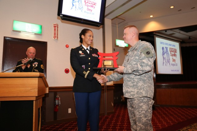 Maj. Lyndsey Thompson, executive officer for the 441st Military Intelligence Battalion, receives a Torri plaque from Col. Stephen Grabski, deputy commander of USARJ, for her participation as keynote speaker during the observance for Women's Equality Day held Aug. 26 at Camp Zama Community Club. (U.S. Army photo by Lance D. Davis)