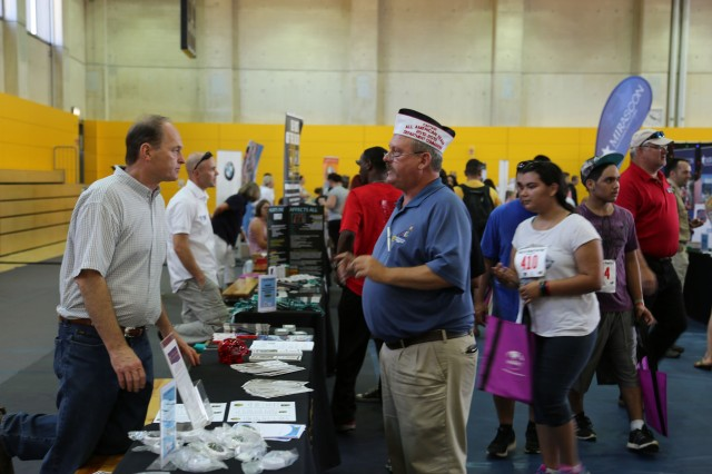 ANSBACH, Germany (Aug. 31, 2016) -- John Hartman, with Army Community Service, talks to community members. Many different on- and off-post organizations took part in the Community Showcase at U.S. Army Garrison Ansbach to meet with community members at the Katterbach Fitness Center. The Back-to-School Fun Run preceded the annual showcase, wherein several participants in the child, youth, and adult categories won prizes. (U.S. Army photo by Bryan Gatchell, USAG Ansbach Public Affairs)