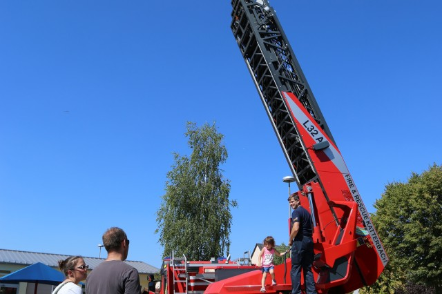 ANSBACH, Germany (Aug. 31, 2016) -- Charles and Moriah Fuller, left, watch their daughter Hannah leave the USAG Ansbach's hydraulic emergency ladder under the guidance of Stefan Groetschel, chief of USAG Ansbach's Fire and Emergency Service. Many different on- and off-post organizations took part in the Community Showcase at U.S. Army Garrison Ansbach to meet with community members at the Katterbach Fitness Center. The Back-to-School Fun Run preceded the annual showcase, wherein several participants in the child, youth, and adult categories won prizes. (U.S. Army photo by Bryan Gatchell, USAG Ansbach Public Affairs)