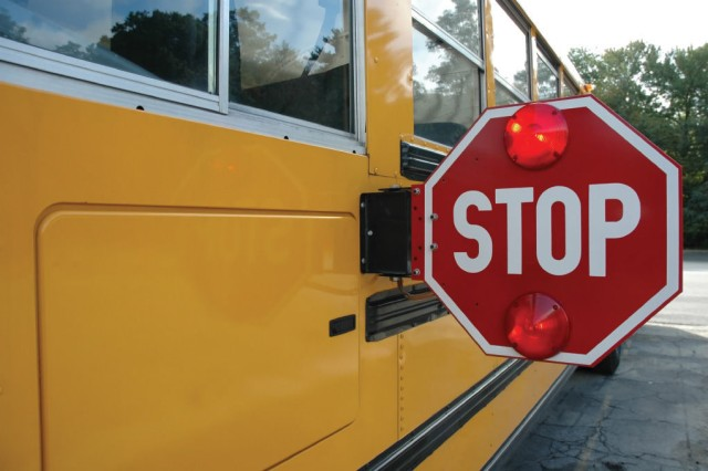 "A stopped school bus displays an extended stop sign with flashing red lights, meant to halt motorists. ""Drivers need to be mindful both on and off base,"" said Lt. Troy Dennison, chief of operations for JBM-HH police. Motorists must stop behind or in front of school buses stopped with flashing red lights until everyone has gotten on or off the bus. The aim of the state law is to protect children on their way to or from school."