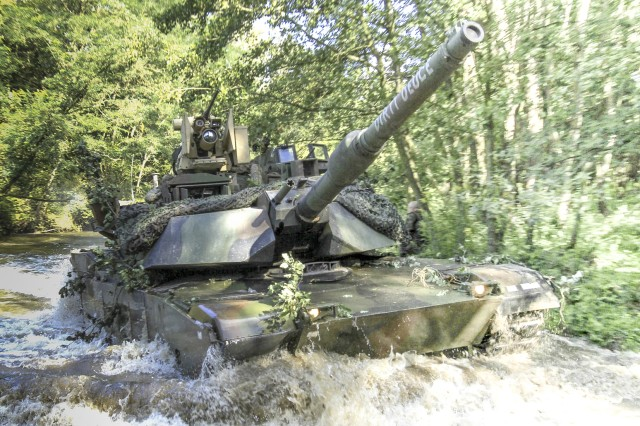 TRZEBIEN, Poland - Concealed among thick foliage, camouflaged faces patiently scanned the water's edge from behind the scope of their M4 carbines. When the signal was given, dismounted troops quietly slipped into the frigid, flowing water and secured the far side of the river, making way for M1A2 Abrams tanks to ford through.