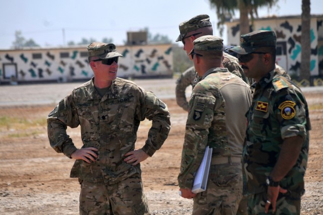 From left, U.S. Army Lt. Col. Shawn Umbrell, commander of 1st Battalion, 502nd Infantry Regiment, Task Force Strike; U.S. Army Capt. Peter Jacobs, commander of Company A, 502nd Infantry Regiment;U.S. Army 2nd Lt. Gideon Bernthal with Company A; and the Iraqi ranger students' commander speak about the day's training July 18, 2016, at Camp Taji, Iraq.