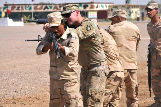 U.S. Army Staff Sgt. Brandon Blanton, center, a trainer with Company A, 1st Battalion 502nd Infantry Regiment, Task Force Strike, assists Iraqi army ranger students during a room clearing drill at Camp Taji, Iraq July 18, 2016. Students were first instructed as a whole by their leadership, then broken into small groups for practice.
