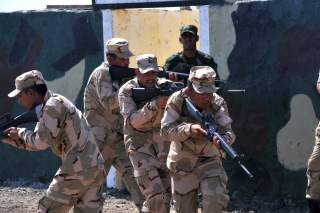 A team of Iraqi army ranger students conducts a glass house room clearing drill as their leadership watches at Camp Taji, Iraq, July 18, 2016. This drill, conducted within a diagram or outline of a building, allows the students to practice room clearing techniques while in full view of their trainers