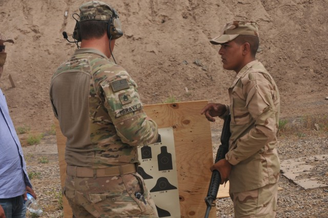 U.S. Army Staff Sgt. William Meravy, left, a trainer with Company A, 1st Battalion 502nd Infantry Regiment, Task Force Strike, discusses with the Iraqi student his qualification score at Camp Taji, Iraq, July 3, 2016. Company A has trained multiple iterations of Iraqi ranger students.