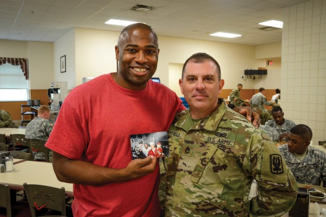 Sgt. 1st Class Jason Mayfield with Shaun Alexander holding a photo of their first encounter 18 years prior.