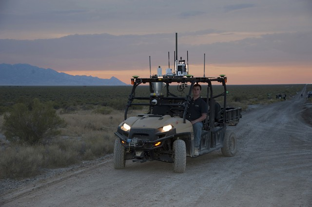 The MDARS four-wheeler platform carries a variety of chemical and biological sensors on its canopy. It is fully autonomous and may be remotely guided into areas of suspected contamination, or assist on-site personnel. At the wheel is Zachery Condon, a software engineer contracted to Edgewood Chemical and Biological Center. Photo by Al Vogel / Dugway Public Affairs.
