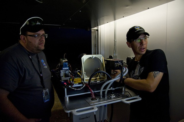 Josh Herron (left), research scientist with Dugway Proving Ground, and Michael Wojcik of the Space Dynamics Lab at Utah State University, prepare a referee standoff detector before a trial. The university has worked with Dugway for eight years, developing accurate referee systems whose data is used as a trusted baseline. Photo by Al Vogel / Dugway Public Affairs