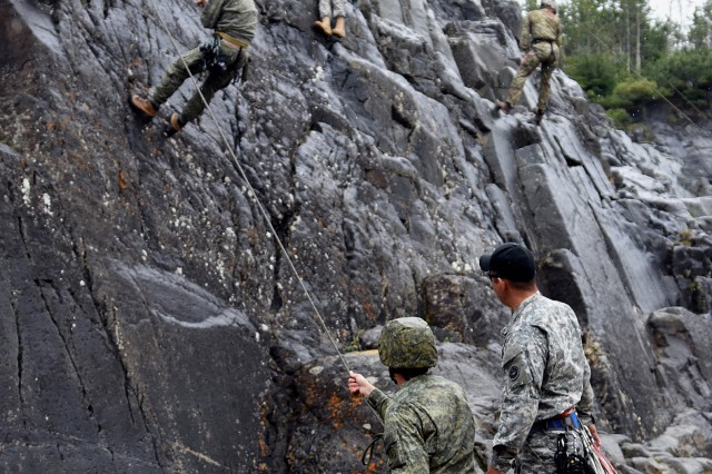 Republic of Kosovo Security Force 1st Lt. Vedat Shaqiri works the belay rope as Cpl. Besim Emini tackles the rock skill training area at the Northern Warfare Training Center's Black Rapids Training Site. Emini and Shaqiri graduated from NWTC's Basic and Advanced Military Mountaineering courses in August. (Army photo/John Pennell)