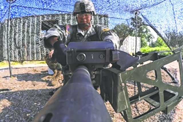 A competitor in the Military Police Competitive Challenge performs a check on the MK-19 Automatic Grenade Launcher.