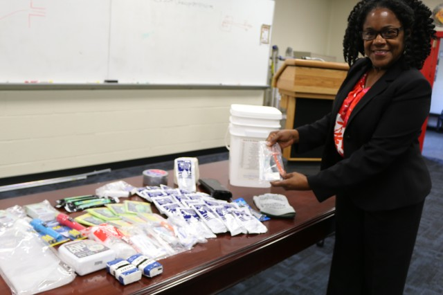 Aviation and Missile Command Emergency Management coordinator Alfreda Alexander shows some of the items in a pre-packaged emergency kit. Duct tape, batteries, light sticks, a can opener, bathroom tissue and a first aid kit are some of the items that should be in an emergency kit. September is National Preparedness Month, Sept. 1, 2016.
