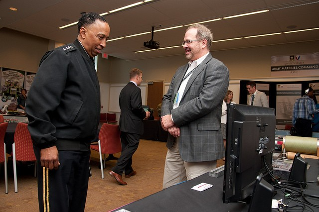 Steve Taulbee, U.S. Army Research Laboratory Weapons and Materials Research Directorate discusses the Advanced Protection Technologies exhibit display with Gen. Dennis L. Via, U.S. Army Materiel Command, during the Army Innovation Summit 3.