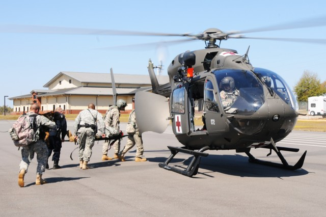 Soldiers and emergency response personnel evacuate a simulated casualty from a previous active shooter force protection exercise.