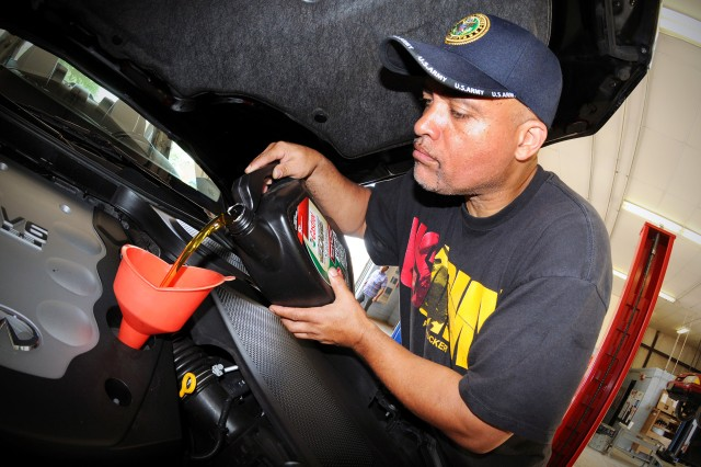 Retired Army Sgt. 1st Class John Neeland tops off the oil in his vehicle at Fort Rucker's Auto Skills Center.