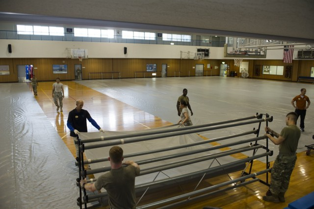 Soldiers and Yano Fitness Center employees prepare the gym for the EEC setup exercise conducted by USAG Japan DPTMS Aug. 31 at Yano Fitness Center. (U.S. Army photo by Alia Naffouj)