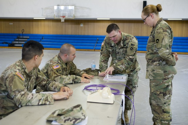 Soldiers review the paperwork at the DES station during the EEC setup exercise conducted by USAG Japan DPTMS Aug. 31 at Yano Fitness Center. (U.S. Army photo by Alia Naffouj)