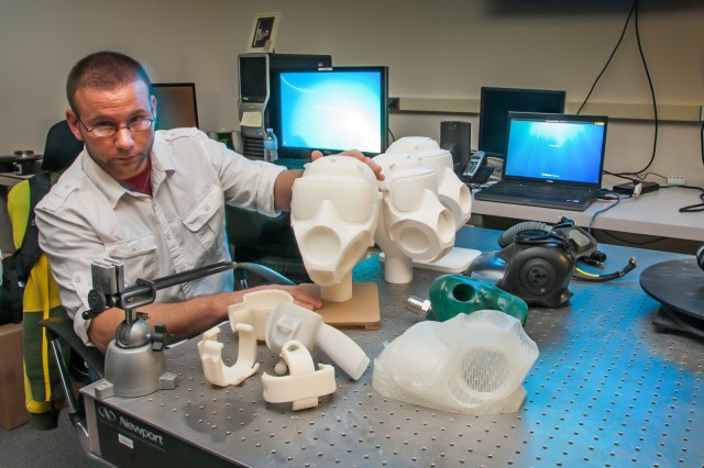 3-D modeling artist Ryan Gilley displays some of the products he designed and printed using advanced manufacturing techniques at the U.S. Army Edgewood Chemical Biological Center's Rapid Technologies Branch.