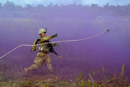"Pvt. Juan Robles, with A Company, 7th Brigade Engineer Battalion, throws a grappling hook to clear tripwires and booby traps in a minefield during the ""in-stride breach"" lane at Hammer Battalion's Sapper Stakes competition, Aug. 25, on Fort Drum, N.Y."