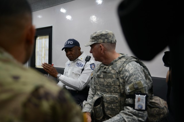 Deputy Inspector Michael Telfer, Transit Counterterrorism Coordinator with the City of New York Police Department, on the left, meets with Lt. Col. Peter Riley, commander of Joint Task Force Empire Shield, Aug. 16, 2016, in a tactical communications vehicle parked near the World Trade Center complex in New York City.