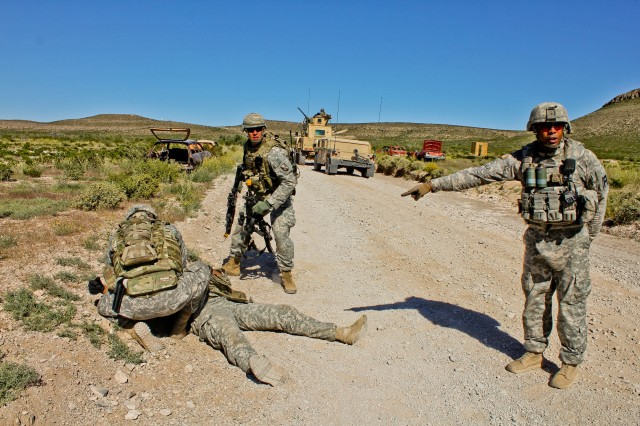 Staff Sgt. Brendon S. Domingo (right), a First Army observer coach/trainer works with members of the  Louisianan National Guard's 927th Engineer Company as they prepare to receive a casualty during a simulated medical evacuation at McGregor Range, N.M.