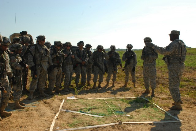 Standing beside a sand table, a First Army observer coach/trainer goes over tactical and technical training procedures of Army National Guard units participating in annual training at the eXportable Combat Training Capability at Fort Chafee, Ark.