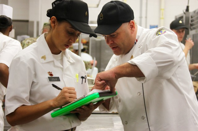 """Sgt. 1st Class David Marcelli, the noncommissioned officer in charge of the 25th Infantry Division Consolidated Dining Facility """"Sustainment Bistro,"""" discusses with Sgt. Cyd Leslie, a culinary arts noncommissioned officer with Headquarters and Headquarters Company, 130th Engineer Brigade, 8th Theater Sustainment Brigade, on how the kitchen staff is performing Aug. 30, during the Phillip A. Connelly Awards Program competition. After competing in and winning the U.S. Army Pacific level of the Phillip A. Connelly, the Culinary Arts Specialists have been selected to compete for the Department of the Army level later this year."""