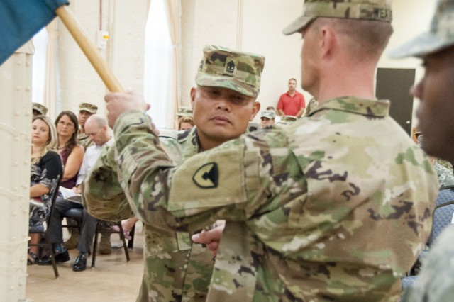 1st Sgt. Efren Delpilar, U.S. Army Sustainment Command Headquarters and Headquarters Company, passes the company's colors during a change of responsibility ceremony in Heritage Hall, Rock Island, Illinois, Sept. 8.