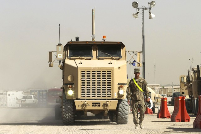 Pfc. Desmond Jones, a motor transport operator with the 109th Transportation Company, 553rd Combat Sustainment Support Battalion, 17th Sustainment Brigade, 1st Sustainment Command (Theater), ground guides a Heavy Equipment Transport at Camp Arifjan, Kuwait, June 9, 2016. HETs are over 50 feet long and have an extremely wide turning radius which makes driving them a challenge.