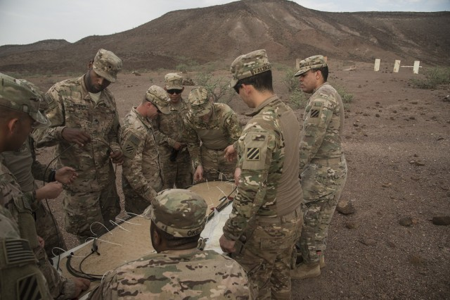 U.S. Army Soldiers from the Bravo Company, 3rd Battalion, 15th Infantry Regiment, place M14 time fuse cords around a piece of cardboard for demolition training, Aug. 30, 2016, in Arta, Djibouti. Bravo Co. 3/15 Inf. Rgt., from Fort Stewart, Ga., serves as the East Africa Response Force assigned to Combined Joint Task Force-Horn of Africa to provide rapid response and security to protect embassies and foreign assets in the area of responsibility of CJTF-HOA. (U.S. Air Force photo by Staff Sgt. Tiffany DeNault)