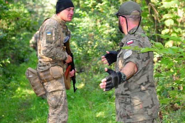 A Polish Soldier assigned to the 21st Podhale Riflemen Brigade instructs a Ukrainian Soldier during react to ambush training, Sept. 8, at the International Peacekeeping and Security Center in Ukraine. The Polish forces recently partnered with the American Army to train Ukrainian Soldiers at the Joint Multinational Training Group-Ukraine. JMTG-U is an example of multinational partners working together to help build the training capacity of the Ukrainian land forces. (Photo by Army Staff Sgt. Elizabeth Tarr)
