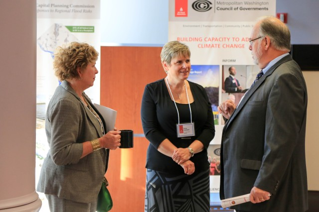 Stacey Underwood, U.S. Army Corps of Engineers, Baltimore District, Silver Jackets Program coordinator and summit panelist, speaks with attendees during a poster session at the 2016 DC Flood Summit held at Gallaudet University, Washington, Sept. 8, 2016.