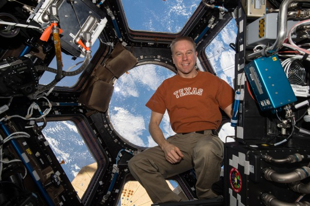Commander Tim Kopra, from Austin, Texas, poses inside the cupola as the station orbits over the Earth below, May 2016.