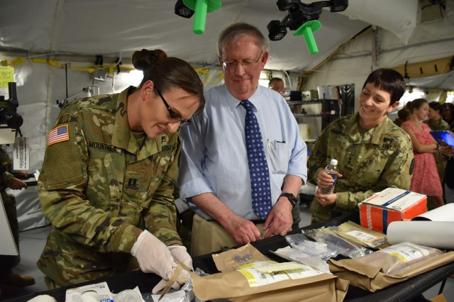 Dr. Vic Macdonald, product manager for USAMMDA's Pharmaceutical Systems Project Management Office, demonstrates the use of freeze-dried plasma for Maj. Gen. Barbara Holcomb, commanding general of the U.S. Army Medical Research and Materiel Command during the VIP Medical Lanes Display at Fort Detrick, Maryland.