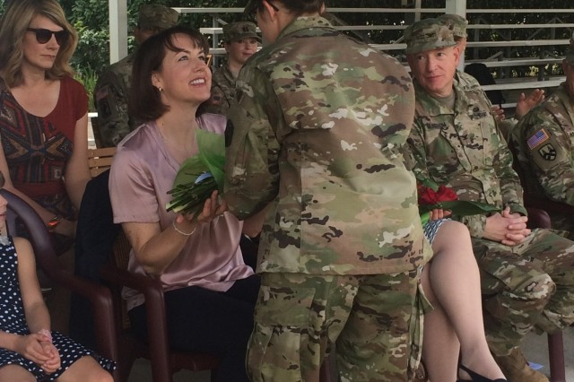 Laura Varhola is presented with a bouquet of yellow flowers to welcome her into the 2500th Digital Liasion Detachment during a ceremony Sunday, September 11, 2016 at Hoekstra Field, on Caserma Ederle in Vicenza, Italy. Her husband,  Col. Christopher Varhola, took command of the 2500th Digital Liaison Detachment from Col. David Mundfrom. Brig. Gen. Steven W. Ainsworth, the commanding general of the 7th Mission Support Command, presided over the ceremony, passing the unit's guideon from the outgoing to the incoming commander. (Photo by 1st Lt. Julie McCabe)