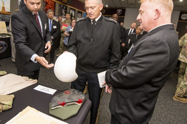 Rob DiLalla (left), an NSRDEC engineer/team leader, briefs Vice Chief of Staff of the Army Gen. Daniel B. Allyn (center) and NSRDEC Director Doug Tamilio (right). Gen. Allyn is holding the Ultra High Molecular Weight Polyethylene Helmet, which was pressed at Natick.