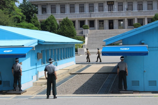 South Korean Soldiers stand guard on the South Korean side of the military demarcation line separating North and South Korea Aug. 16, with two standing partially behind the buildings to reduce their silhouettes, should they be shot at.  North Korean Soldiers march past on the North Korean side of the MDL. (U.S. Army photo by Spc. Jeremy Reuse, 2nd Battalion, 8th Cavalry Regiment, 1st Armored Brigade Combat Team, 1st Cav. Div.)