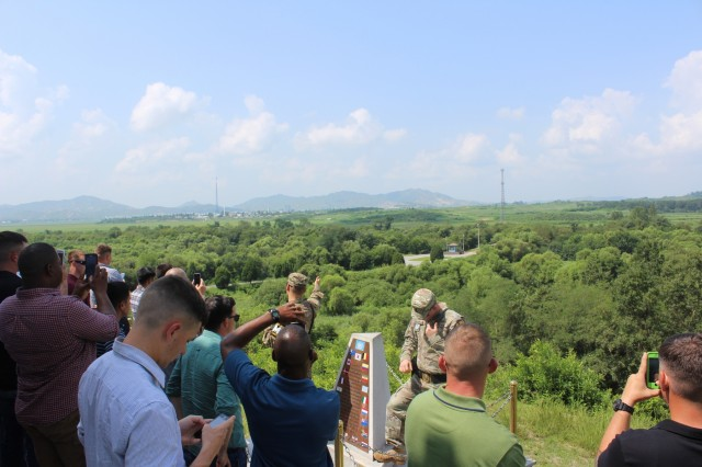 """Soldiers from 2nd Battalion, 8th Cavalry Regiment """"Stallions,"""" 1st Armored Brigade Combat Team, 1st Cavalry Division listen and take photos of the """"Bridge of No Return"""" and Kijong-dong """"peace village"""" in North Korea, while U.S. Army military police explain the significance of these sites. Soldiers visited Camp Bonifas, South Korea, as well as the Joint Security Area in the Korean Demilitarized Zone, the """"Bridge of No Return"""" and several other points of interest, during a tour Aug. 16. (U.S. Army photo by Spc. Jeremy Reuse, 2nd Battalion, 8th Cavalry Regiment, 1st Armored Brigade Combat Team, 1st Cav. Div.)"""