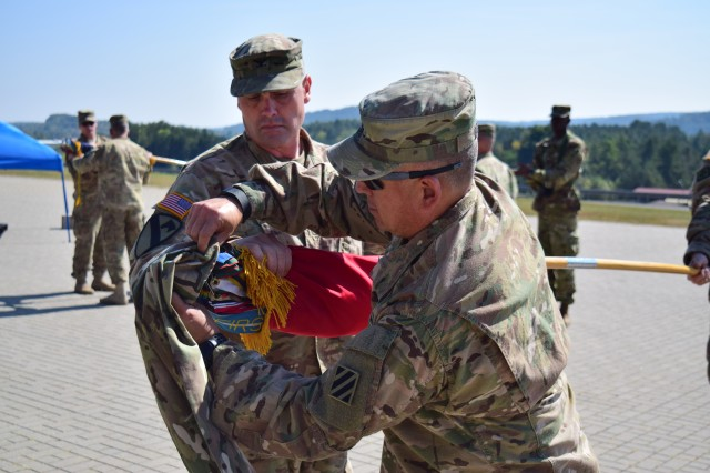 Col. Phil Brooks (left), the commander for 1st Armored Brigade Combat Team, 3rd Infantry Division, and Command Sgt. Maj. James Wafe (right) the brigade's senior enlisted advisor, case the brigade colors during a ceremony at Hohenfels Training Area, Germany September 15. The ceremony signifies the end of the brigade's time as the regionally allocated force for U.S. European Command. (U.S. Army photo by Spc. Ryan Tatum)
