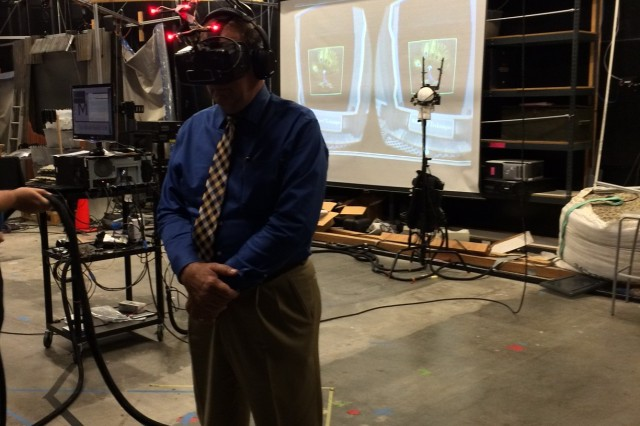 """During a visit to the Institute for Creative Technologies, Bryon J. Young, ACC-APG's executive director, uses the """"Redirected Walking"""" headset.  This tool is a perceptual trick that slowly guides users in circles while making them think they're exploring a far larger space."""