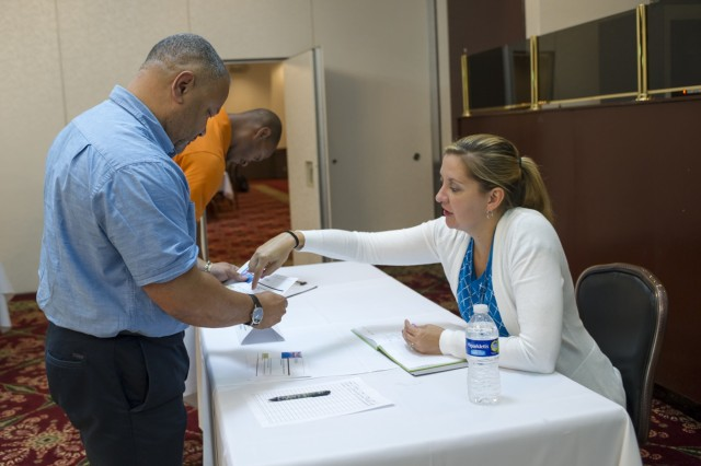 Melvin Jackson speaks with Brianna Kluckman from United Services for Japan Officials Association during the job fair portion of the ACS Spouses and Family Member Employment Training Symposium and Job Fair held Sept. 13 at the Camp Zama Community Club. (U.S. Army photo by Alia Naffouj)