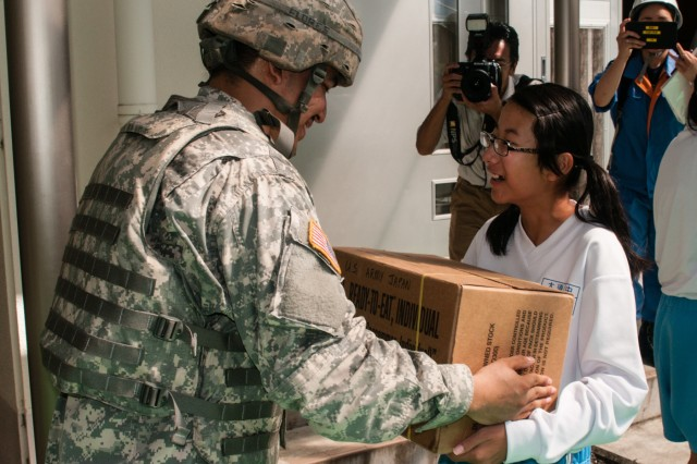 Army Spc. Ruben A. Flores, an Atlanta, Georgia, native serving as a preventative medicine specialist for Public Health Command-Pacific, hands a box of Meals Ready to Eat packages to a student from Osuka Junior High School in Kakegawa, Japan, Sep. 4, 2016. Flores and 11 other U.S. Army Soldiers participated in Shizuoka Prefecture's annual Comprehensive Disaster Drill. The drill demonstrated how a diverse collection of local, regional, national and international organizations can pool their respective resources to effectively respond to a major disaster. In addition to distributing supplies, the contingent of U.S. Army troops collaborated with their JGSDF counterparts to coordinate convoy routes, establish mobile communication sites and provide casualty care. (Photo by Sgt. John L. Carkeet IV, U.S. Army Japan)