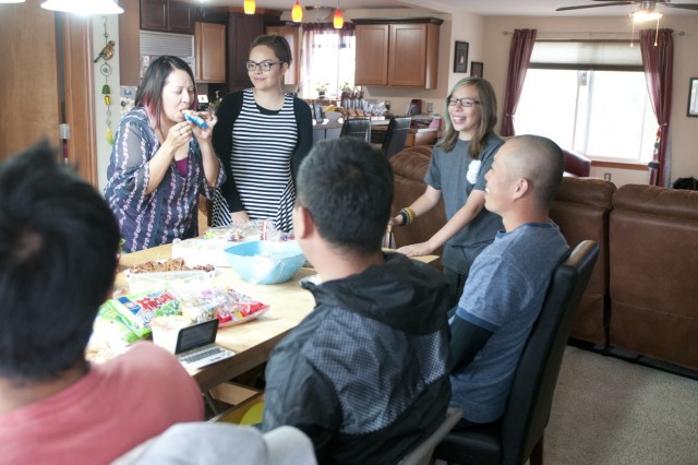 Raquel Kesselring tries a bite of a Japanese snack bar as her children, Ashley and Cameron, wait for her reaction, Sep. 17. Sergeants Yogo Zukeyama, Takuya Homura and Yoshiyuki Nakahama, members of the 12th Regiment, Japan Ground Self-Defense Force, brought an assortment of Japanese gifts for their host family to enjoy. (U.S. Army photo by Sgt. Uriah Walker, 5th Mobile Public Affairs Detachment) 160917-A-AP855-115