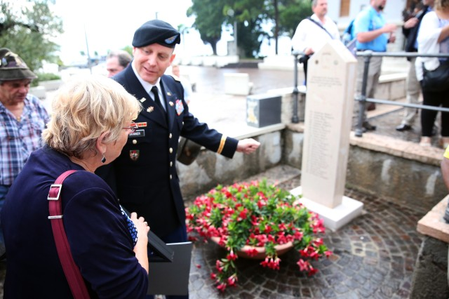 "U.S. Army Lt. Col. Brent Skinner, commander of the 509th Signal Battalion, shows Joanne Lien a monument for her father, Pfc. Frank Miller, and 24 other Soldiers from the 10th Mountain Division, after a remembrance ceremony Sept. 15, 2016 in Torbole, Italy. ""We're here to honor our fallen comrades and Soldiers,"" Skinner said."